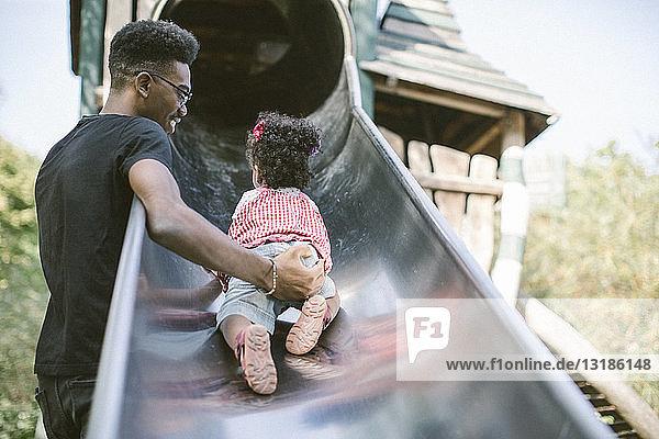 Vater unterstützt Tochter  die auf einer Rutsche auf dem Spielplatz hochkrabbelt