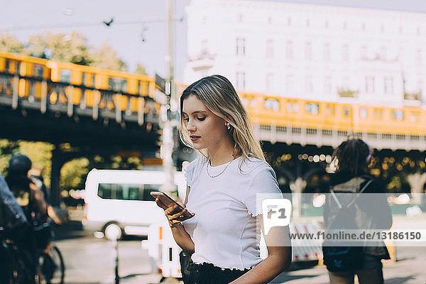Junge Frau benutzt Mobiltelefon beim Gehen auf der Straße in der Stadt