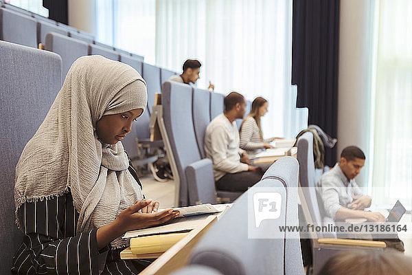 Seriöse Frau im Hijab liest Buch von Studenten im Hörsaal der Universität