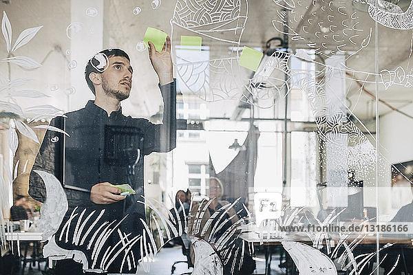 Junger kreativer Geschäftsmann klebt Klebezettel auf gemustertes Glas im Büro