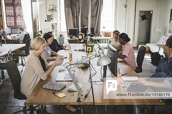 Kreative Geschäftsleute  die an Schreibtischen im Büro arbeiten