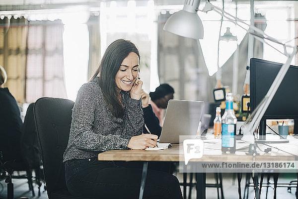 Kreative Geschäftsfrau lächelt beim Schreiben im Notizblock am Schreibtisch