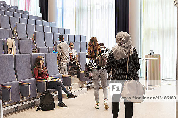 Smiling students looking at friends walking towards chairs in lecture hall at high school