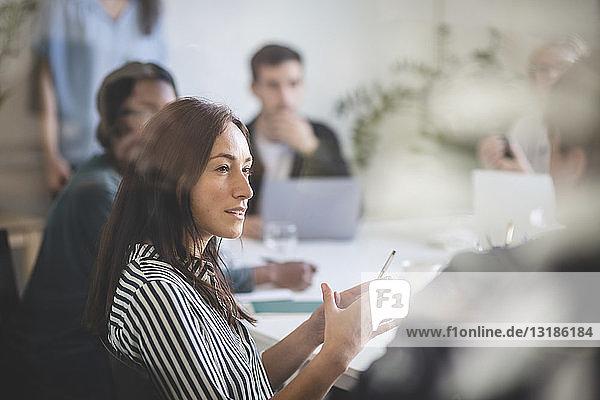 Geschäftsfrau erklärt Kollegen während einer Brainstorming-Sitzung im Kreativbüro