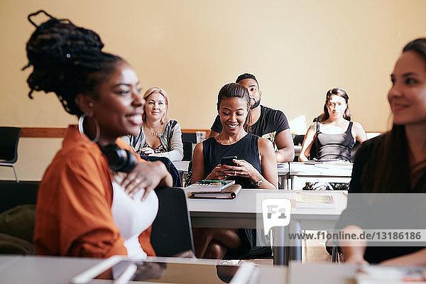 Reife Frau benutzt Smartphone  während sie mit Klassenkameraden im Sprachunterricht sitzt