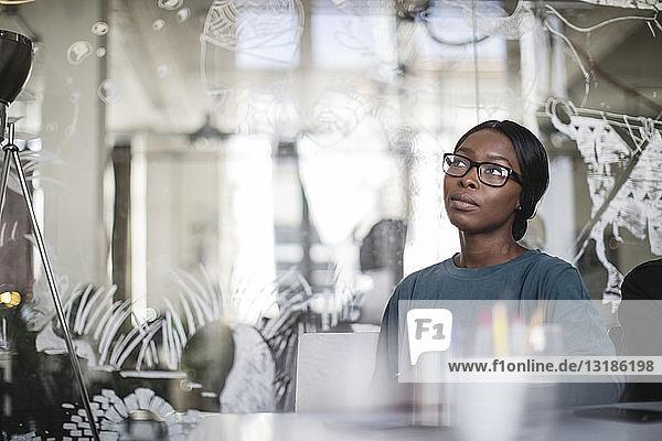 Junge Geschäftsfrau hört zu  während sie in einem kreativen Büro am Konferenztisch sitzt