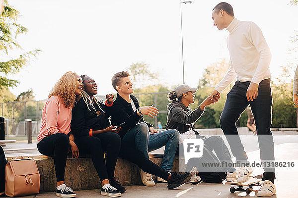 Glückliche Freunde begrüßen Mann mit Skateboard im Park