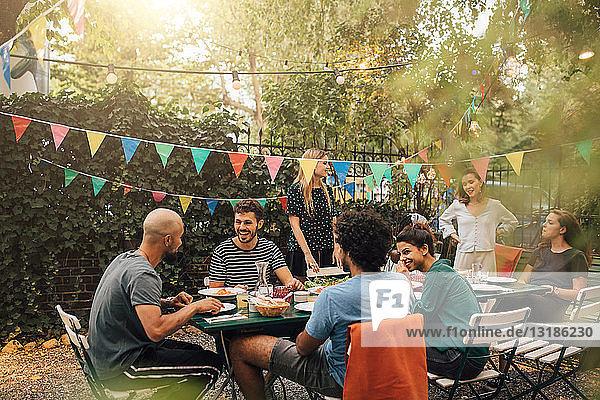 Glückliche multiethnische Freunde unterhalten sich beim Abendessen während einer Gartenparty
