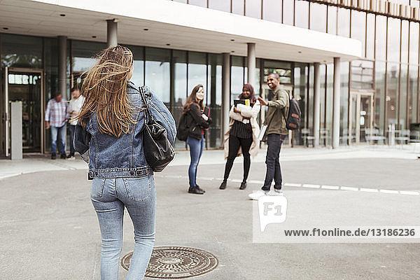 Rückansicht einer Frau  die auf Freunde auf dem Universitätscampus zugeht