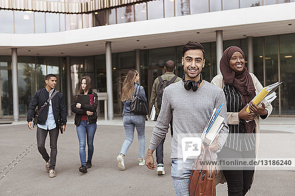 Porträt eines lächelnden Studenten  der Bücher hält  während er mit Freunden im Hintergrund über den Campus läuft