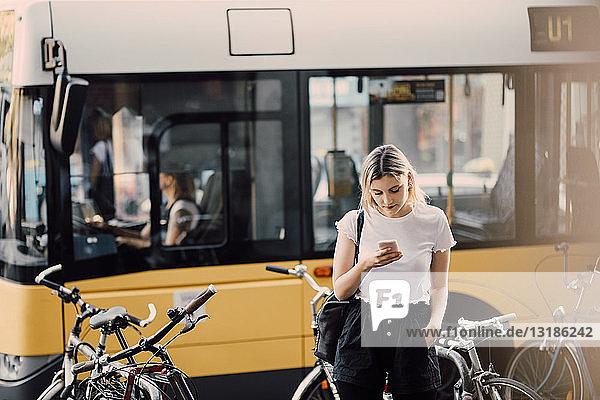 Junge Frau benutzt Smartphone  während sie in der Stadt an Fahrrädern gegen den Bus steht