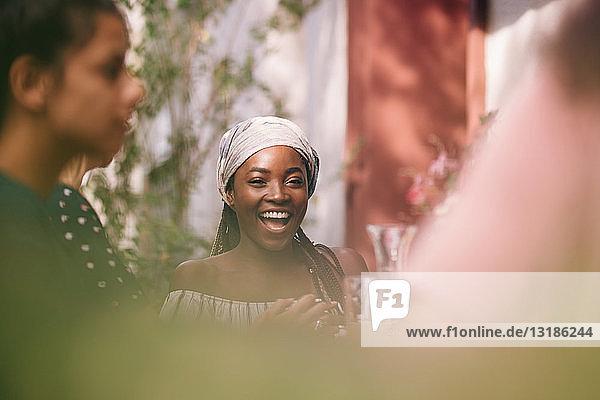 Porträt einer fröhlichen jungen Frau  die bei einer Tischgartenparty sitzt