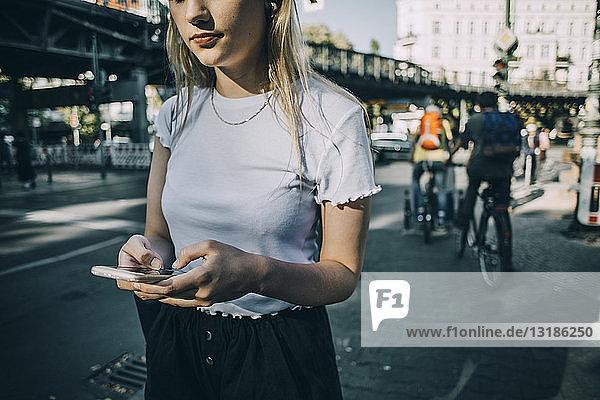 Mitschnitt einer jungen Frau  die ein Smartphone benutzt  während sie in der Stadt auf dem Bürgersteig steht