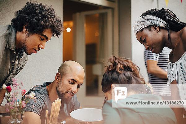 Neugierige multiethnische männliche und weibliche Freunde schauen während der Dinnerparty nach unten