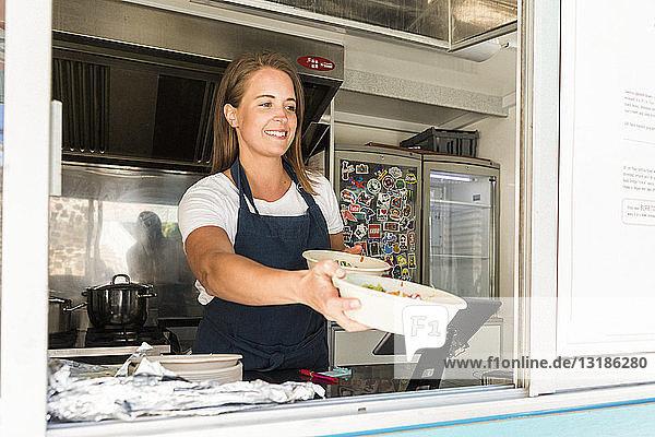 Lächelnde junge Besitzerin gibt Schüsseln ab  während sie im Speisewagen steht