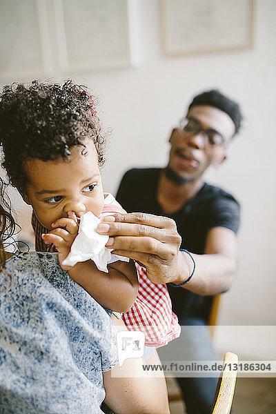 Junger Mann wischt einer Tochter den Mund ab  die zu Hause von einer Frau gehalten wird