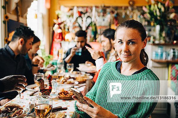 Porträt einer selbstbewussten jungen Frau  die ein Smartphone in der Hand hält  während sie mit Freunden am Tisch im Restaurant während des Abendessens sitzt