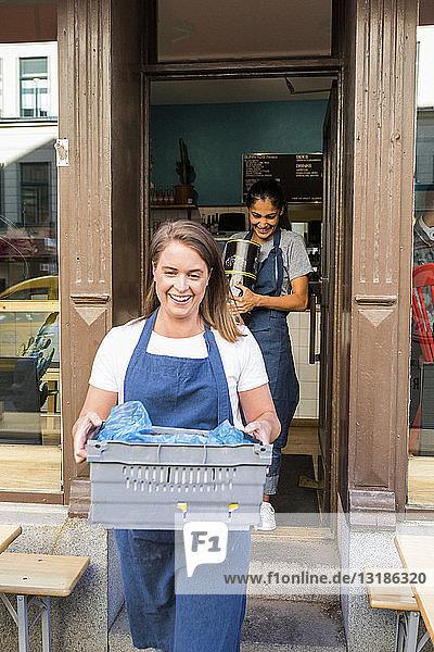 Lächelnde Besitzerinnen tragen Kisten gegen Restaurant