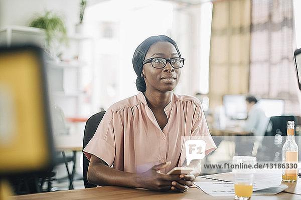 Kreative junge Geschäftsfrau schaut weg  während sie ihr Handy am Schreibtisch im Büro hält