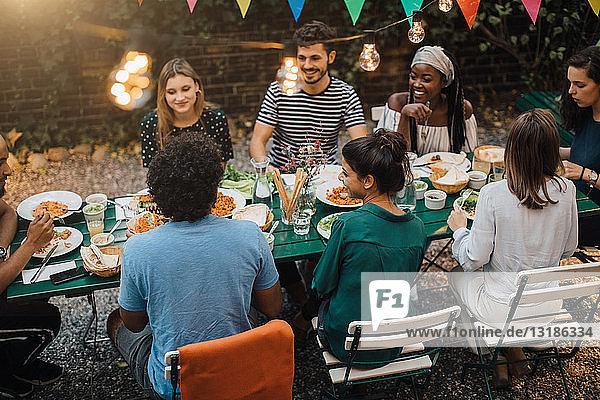 Schrägaufnahme von multi-ethnischen jungen Freunden  die während einer Gartenparty am Tisch zu Abend essen