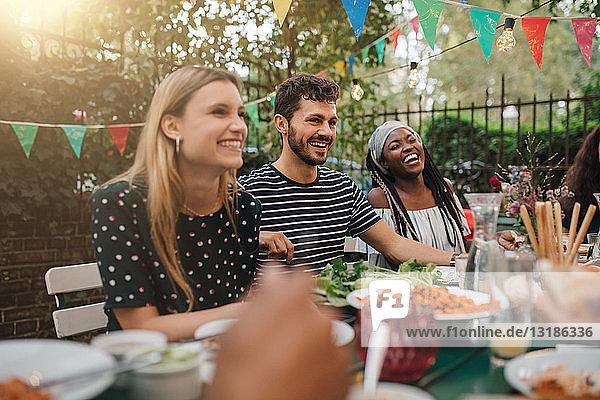 Glückliche multiethnische Freunde genießen das Abendessen am Tisch während der Gartenparty