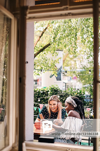 Glückliche multiethnische Freundinnen  die durch ein Fenster auf ein Mobiltelefon schauen