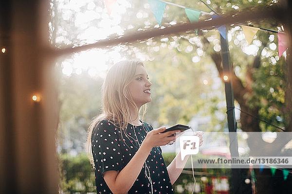 Lächelnde junge Frau spricht während der Party durch Kopfhörer auf dem Balkon
