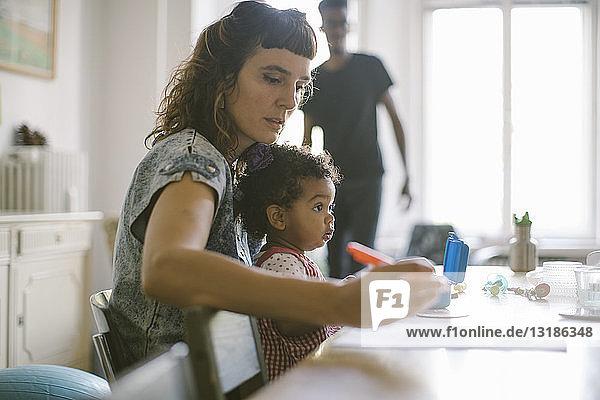 Frau arbeitet  während sie mit ihrer Tochter im Haus am Tisch sitzt