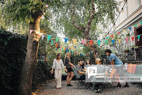 Multiethnische männliche und weibliche Freunde genießen während einer Gartenparty im Garten