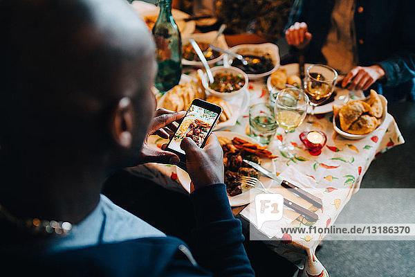 Hochwinkelaufnahme eines jungen Mannes  der während einer Dinnerparty im Restaurant sitzend Essen auf einem Teller fotografiert