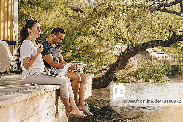 Mature couple using laptops while sitting at patio in holiday villa