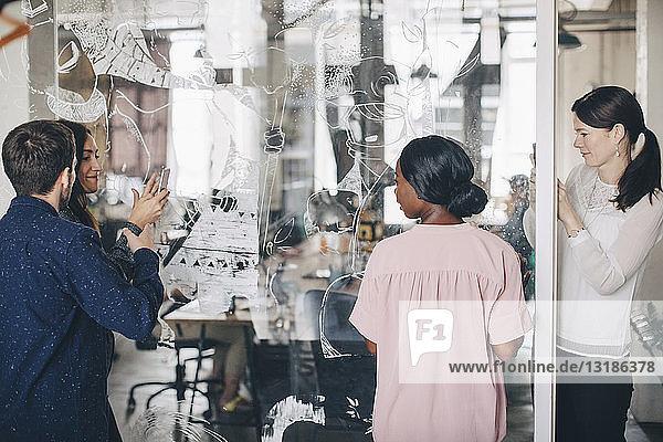 Unternehmer  die weibliche Kollegen beim Fotografieren über Mobiltelefone im Büro beobachten