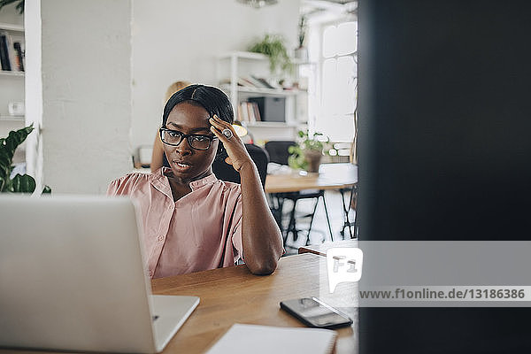 Angespannte junge Geschäftsfrau betrachtet Laptop am Schreibtisch im Büro