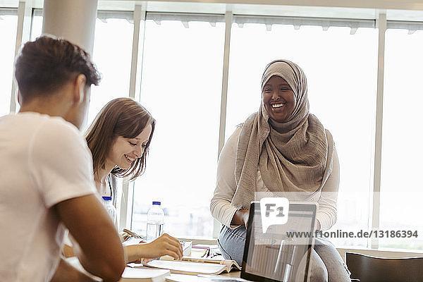 Lächelnde Universitätsstudenten studieren gemeinsam im Klassenzimmer