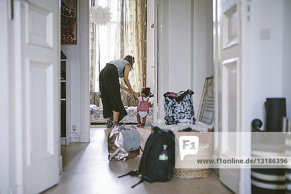 Mother assisting daughter in walking seen through doorway at home