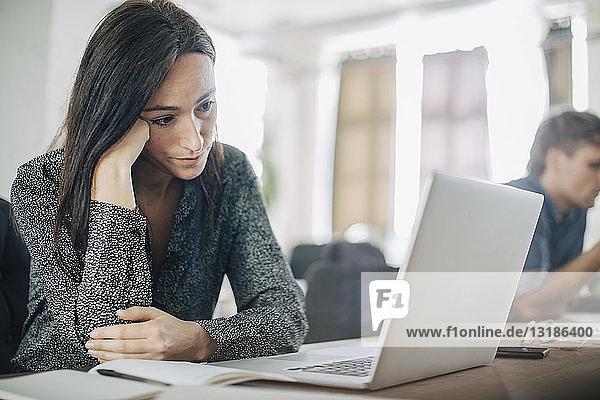Müde Geschäftsleute schauen auf den Laptop  während sie im Kreativbüro am Schreibtisch sitzen