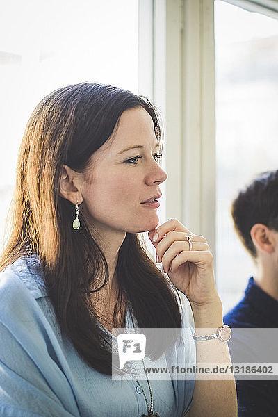 Kreative Geschäftsfrau blickt weg  während sie im Büro am Fenster steht