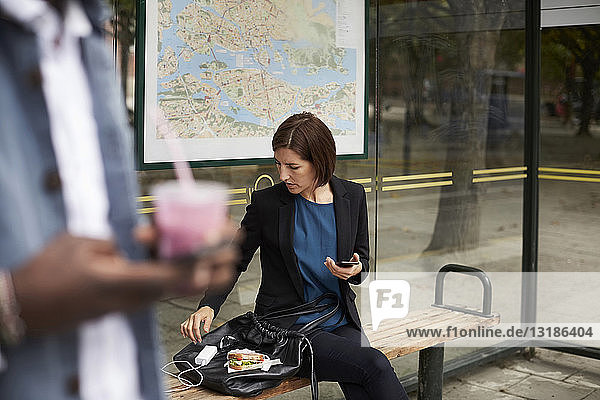 Businesswoman eating sandwich while sitting at bus stop in city