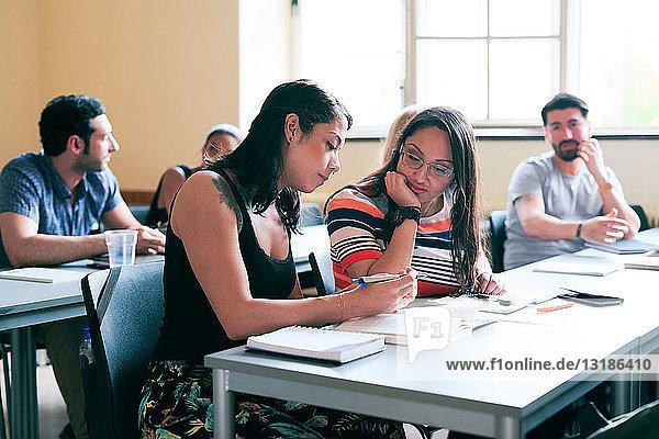 Studentinnen diskutieren über den Unterricht  während sie im Klassenzimmer am Schreibtisch sitzen