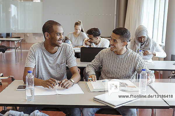 Lächelnde männliche Freunde unterhalten sich beim Lernen im Klassenzimmer an der High School