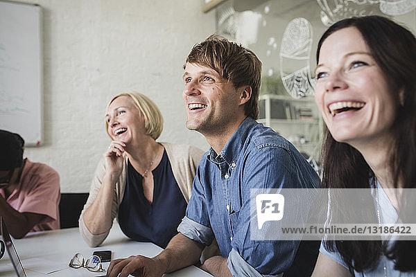 Lächelnde kreative Geschäftsleute  die während einer Besprechung im Konferenzraum sitzen und zuhören