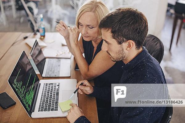 Computerprogrammierer erklärt seiner Kollegin am Laptop am Schreibtisch im Kreativbüro
