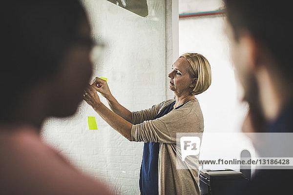 Unternehmer betrachten eine Kollegin  die im Kreativbüro einen Haftzettel auf Glas klebt