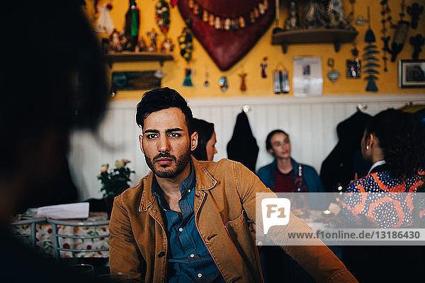 Junger Mann sieht Freund an  während er im Restaurant beim Brunch gegen Frauen sitzt