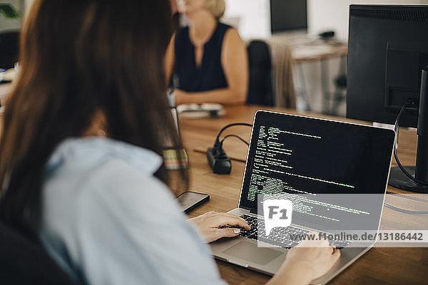 Computerprogrammiererin  die am Schreibtisch im Kreativbüro arbeitet