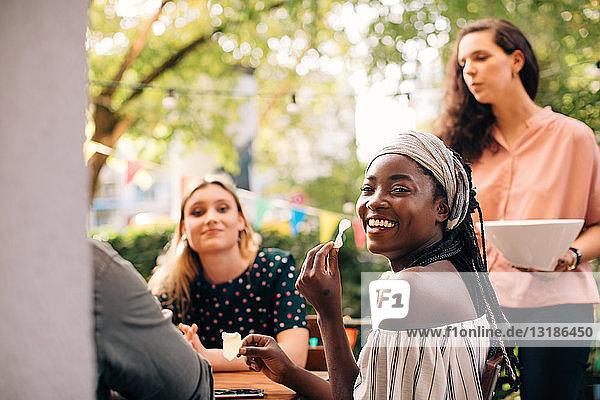 Porträt einer lächelnden jungen Frau  die mit Freunden auf dem Balkon Snacks isst