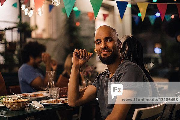 Porträt eines lächelnden jungen Mannes mit rasiertem Kopf  der während einer Dinnerparty im Hinterhof am Tisch sitzt