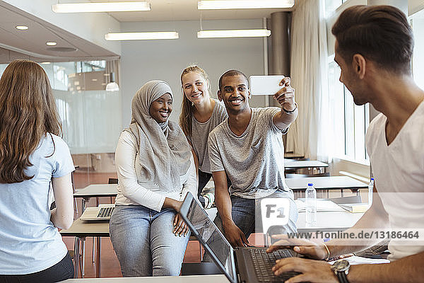 Students looking at friends taking selfie in university classroom