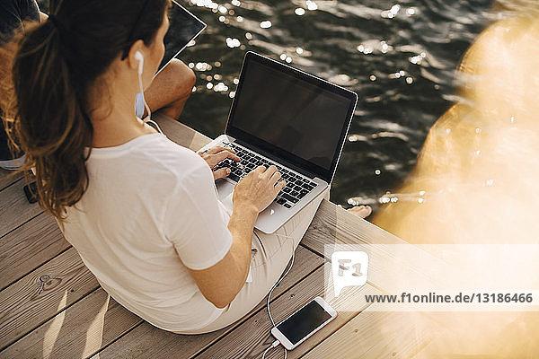 Hochwinkelansicht einer Frau  die einen Laptop benutzt  während sie mit einem Mann auf der Terrasse einer Ferienvilla sitzt