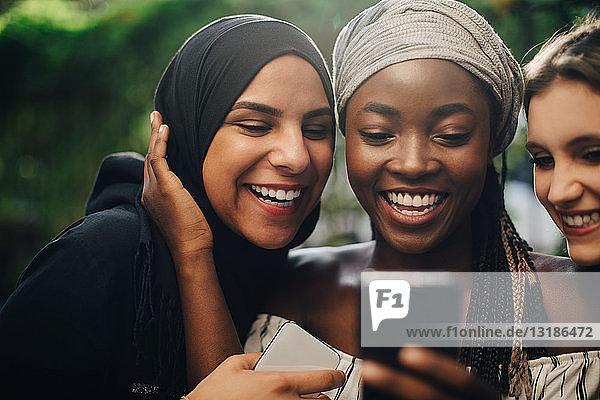 Lächelnde multiethnische Freunde  die im Hinterhof stehen und auf ihr Handy schauen